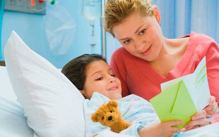 Child patient reading a get well card with her mom