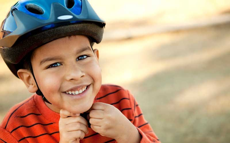 Young boy smiling as he puts on a bike helmet