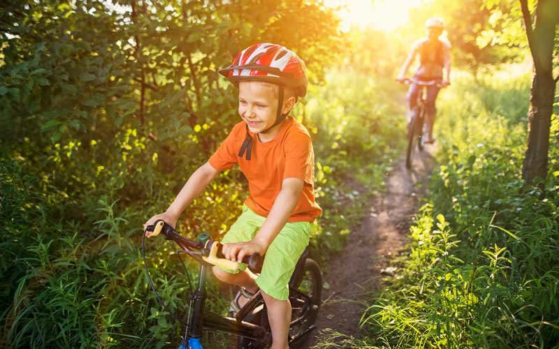 Young boy riding a bike through the woods with a friend